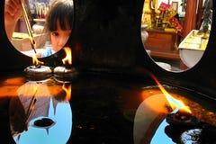 Children make merit by set on joss stick. Stock Photos