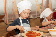 Children make pizza. Little cook. Little cook. Children make pizza. Master class for children on cooking Italian pizza. Young children learn to cook a pizza stock photo