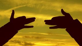 Children make shape of dog shape with hands at sunset. girls hold the gesture of a dog symbol with their fingers against. Sky. children show with hands the stock video footage