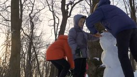 Children make snowman together in winter park. Children make a snowman in winter park. The brothers spend their leisure time outdoors together. Camera in motion stock video
