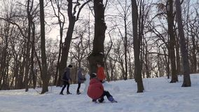 Children make snowman in winter park, slow motion. Children make a snowman in winter park. The brothers spend their leisure time outdoors together. Camera in stock footage