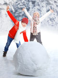 Children make a snowman in winter time Stock Images
