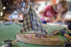 Children make wooden ships. Children make wooden sailing boats in a club workshop royalty free stock photo