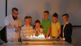 Children looks at dancing fiery loudspeaker. Children makes experiment with Ruben`s tube. The fire is dancing to the beat of music in flame tube. Fascinating stock video footage