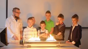Children looks at music fiery loudspeaker. Children makes experiment with Ruben`s tube. The fire is dancing to the beat of music in flame tube. Fascinating stock video footage