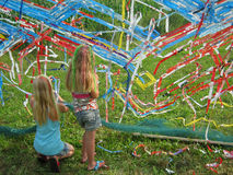 Children making artwork. During summer holiday many festivals are organised for children to keep them amused. Two girls are twining plastic ribbons in a grid to Royalty Free Stock Photo