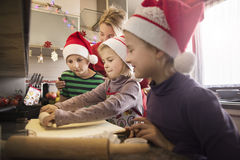 Children making Christmas cookies with their mother stock photos