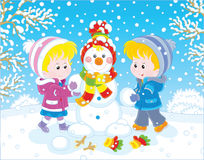 Children making a Christmas snowman royalty free illustration