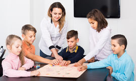 Children making move on pre-marked surface of board game. American children making move on pre-marked surface of board game at classroom Stock Photo