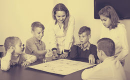 Children making move on pre-marked surface of board game. At classroom Royalty Free Stock Photos