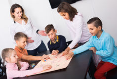 Children making move on pre-marked surface of board game. European children making move on pre-marked surface of board game at classroom Stock Photo