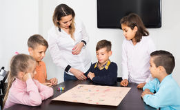 Children making move on pre-marked surface of board game. Happy american children making move on pre-marked surface of board game at classroom Stock Photography