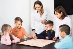Children making move on pre-marked surface of board game. Happy children making move on pre-marked surface of board game at classroom Royalty Free Stock Photo