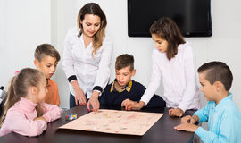 Children making move on pre-marked surface of board game. Happy russian children making move on pre-marked surface of board game at classroom Stock Image
