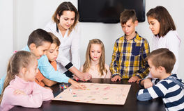 Children making move on pre-marked surface of board game. Happy spanish children making move on pre-marked surface of board game at classroom Stock Images