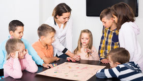 Children making move on pre-marked surface of board game. Positive american children making move on pre-marked surface of board game at classroom Royalty Free Stock Photography