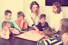 Children making move on pre-marked surface of board game. Positive russian children making move on pre-marked surface of board game at classroom Royalty Free Stock Images