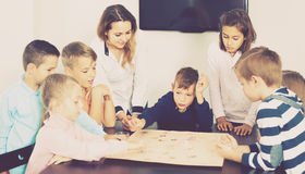 Children making move on pre-marked surface of board game. Positive spanish children making move on pre-marked surface of board game at classroom Royalty Free Stock Photo