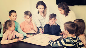 Children making move on pre-marked surface of board game. Smiling american children making move on pre-marked surface of board game at classroom Royalty Free Stock Photo
