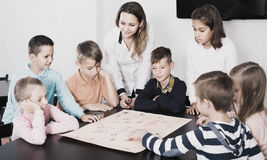 Children making move on pre-marked surface of board game. Smiling children making move on pre-marked surface of board game at classroom Royalty Free Stock Photos