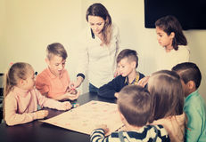 Children making move on pre-marked surface of board game. Smiling european children making move on pre-marked surface of board game at classroom Stock Images
