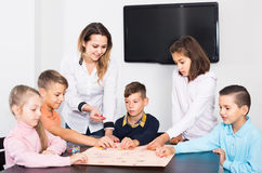 Children making move on pre-marked surface of board game. Smiling spanish children making move on pre-marked surface of board game at classroom Stock Photography