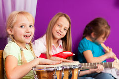 Children making music with instruments at home. Children - sisters - making music at home, they are practicing playing guitar, bongo and flute as instruments Stock Photography