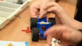 Children making robot from meccano set. Close-up shot of two pupils working with meccano set to make a robot. Robotics at school stock footage