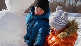 Children making a snowman in the Playground stock footage