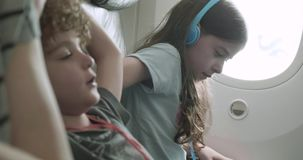 Children making themselves comfortable in a plane seat. Children wearing headphones making themselves comfortable in their plane seats by shifting and moving stock video footage