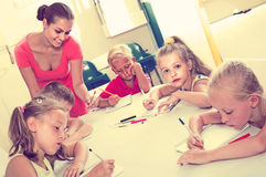 Children making writing exercises with help of teacher in class royalty free stock photo