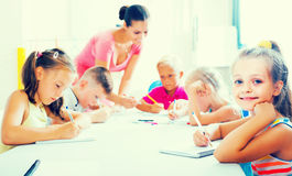 Children making writing exercises with help of teacher in class royalty free stock images