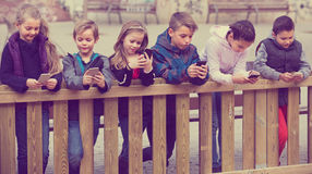 Children with mobile devices. Group of children posing at urban street with mobile devices together royalty free stock image