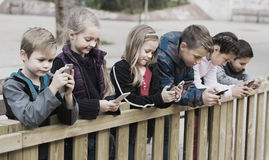 Children with mobile devices. Portrait of children posing at urban street with mobile devices stock photo