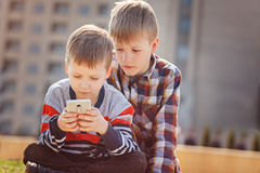 Children with mobile phone outdoor. Boys smiling, looking to phone, playing games or using application Royalty Free Stock Images