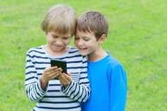 Children with mobile phone outdoor. Two boys smiling, looking to screen, playing games or using application. Technology Royalty Free Stock Images