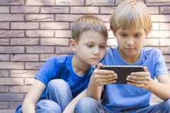Children with mobile phone. Two boys looking at screen, playing games or using application. Outdoor. Technology