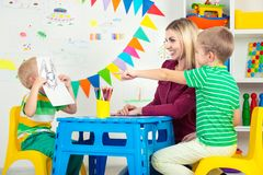 Children with mom and draw pictures in the kids room. Stock Photography
