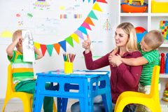 Children with mom draw pictures in the kids room.Have fun together. Family leisure royalty free stock photo