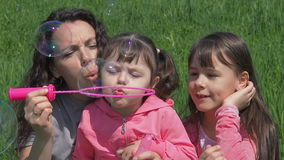 Children with mom on the green grass are blowing soap bubbles. Family in a summer park. Mom and daughters playing in nature on a s. Unny day. Girl with children stock footage