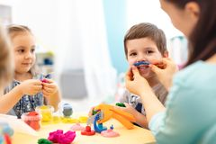 Children and mom or kindergartener make by hands playing with color dough. Kids show imagination and have fun with plasticine. In daycare centre royalty free stock photography