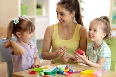 Children and mom make by hands playing with color dough. Children and their mom make by hands playing with color dough royalty free stock image