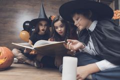 Children in monster costumes sat on the floor, cross-legged and with curiosity consider a spellbook. A girl in a witch suit, a girl in a red dress and a boy in a Stock Photography
