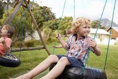 Children At Montessori School Playing On Swings During Break Royalty Free Stock Photos