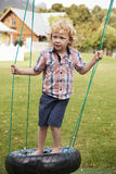 Children At Montessori School Playing On Swings During Break stock photos