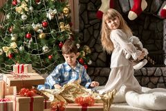 Children in the morning under the Christmas tree dismantled gifts Stock Photos