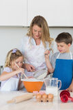 Children with mother baking cookies at counter top. In kitchen Royalty Free Stock Images