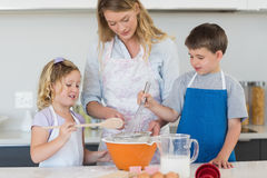 Children and mother baking cookies. At counter top in kitchen royalty free stock photos