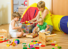 Children and mother collecting toys stock photo