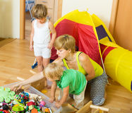 Children and mother collecting toys. Two little girls and mother collecting toys in plastic box Royalty Free Stock Images